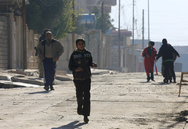 Civilians run for cover upon hearing the sound of clashes between Iraqi forces and Islamic State militants in Wahda district of eastern Mosul, Iraq, January 6, 2017. (Photo by Alaa Al-Marjani/Reuters)