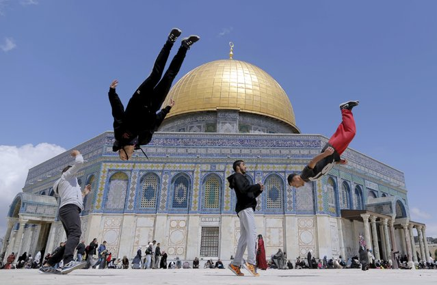 The Dome of the Rock is seen in the background as Palestinian youths practice their parkour skills during Friday prayers in Jerusalem's Old City April 10, 2015. (Photo by Ammar Awad/Reuters)