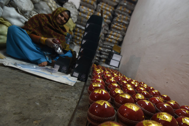In this photograph taken on December 14, 2016, an Indian craftsman inspects new cricket balls at a factory in Meerut, some 70kms north-east of New Delhi. (Photo by Dominique Faget/AFP Photo)