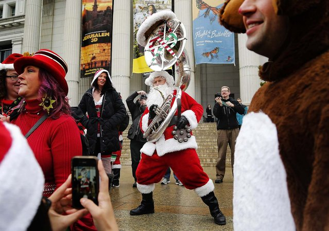 """A tuba-playing Santa Claus joins holiday revelers as they participate in the Santarchy mass gathering on the steps of the National Museum of Natural History in Washington. Organizers call the event, which they say attracts thousands of Santas in cities around the U.S., a """"non-profit, non-political, non-religious and non-sensical celebration of holiday cheer, goodwill and fun"""".  (Photo by Jonathan Ernst/Reuters)"""
