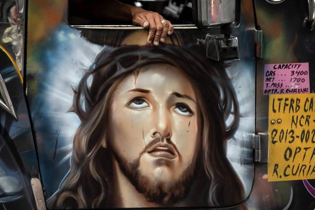 This picture taken on January 13, 2019 shows a depiction of Jesus Christ painted on the door of a jeepney during rush hour in Manila, Philippines. (Photo by Noel Celis/AFP Photo)