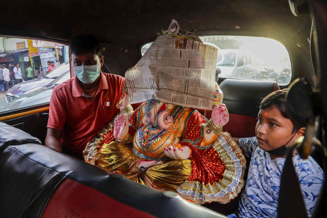An idol of elephant-headed Hindu god Ganesh is transported in a taxi in Kolkata, India, Wednesday, September 8, 2021. The idol is being taken home for worship ahead of Ganesh Chaturthi festival that celebrates the birth of Ganesha. (Photo by Bikas Das/AP Photo)