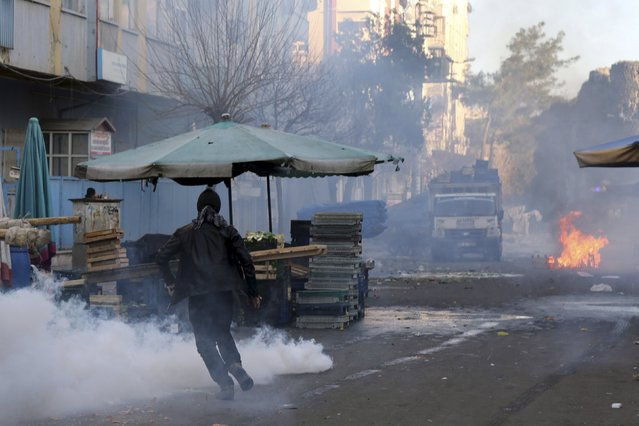 A demonstrator runs to take cover as Turkish riot police use tear gas to disperse Kurdish demonstrators during a protest against a curfew in Sur district and security operations in the region, in the southeastern city of Diyarbakir, Turkey March 2, 2016. (Photo by Sertac Kayar/Reuters)