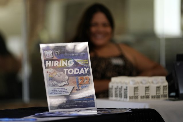 A hiring sign is placed at a booth for prospective employers during a job fair Wednesday, September 22, 2021, in the West Hollywood section of Los Angeles.  The number of Americans applying for unemployment aid rose last week for a second straight week to 351,000, a sign that the delta variant of the coronavirus may be disrupting the job market's recovery, at least temporarily.(Photo by Marcio Jose Sanchez/AP Photo)