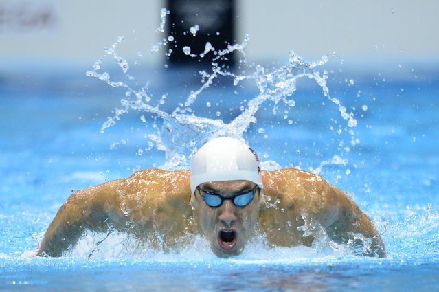 US swimmer Michael Phelps competes in the men's 200m butterfly heats swimming event at the London 2012 Olympic Games at the Olympic Park in London on July 30, 2012. (Photo by Leon Neal/AFP Photo)