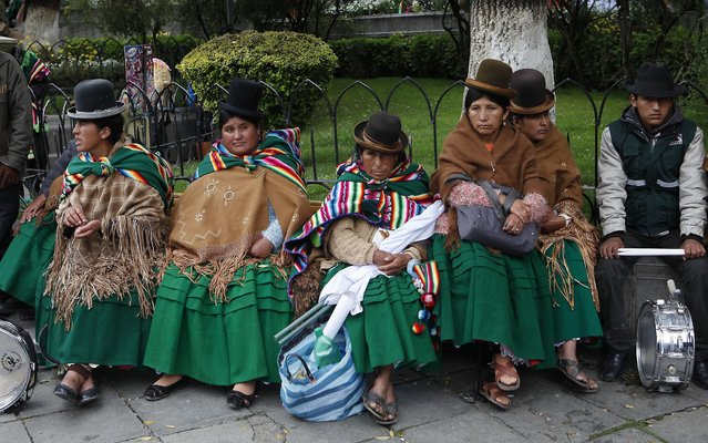 Aymara Indian women listen to Bolivia's President Evo Morales deliver his state-of-the-nation address as they sit outside Congress in La Paz, Bolivia, Wednesday, January 22, 2014. (Photo by Juan Karita/AP Photo)