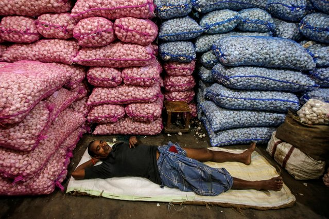 A labourer sleeps at a wholesale vegetable market early morning in Kolkata, March 5, 2019. (Photo by Rupak De Chowdhuri/Reuters)