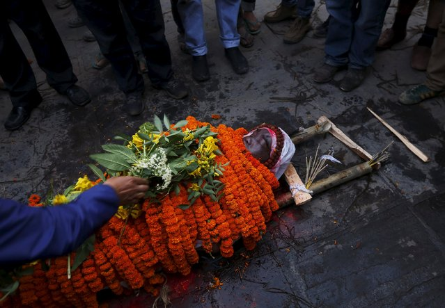A relative places a flower over a body of his family member, who died in Saturday's earthquake, during a cremation along a river in Kathmandu, Nepal April 28, 2015. (Photo by Adnan Abidi/Reuters)