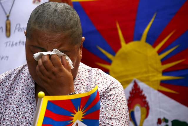 A Tibetan protester cries after she had her head shaved during a rally to mark what organisers said was the 57th anniversary of the Tibetan National Uprising Day in central Sydney, Australia, March 10, 2016. (Photo by David Gray/Reuters)