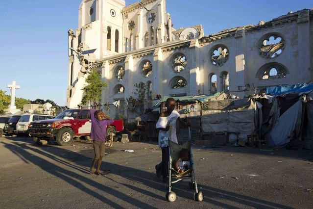 Residents walks next to the ruins of the National Cathedral during the 7th anniversary of the January 2010 earthquake in Port-au-Prince, Haiti. Thursday January 12, 2017. The earthquake caused major damage in Port-au-Prince, Jacmel and other settlements in the region killing tens of thousands. (Photo by Dieu Nalio Chery/AP Photo)