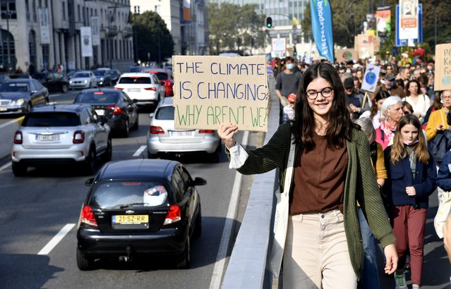A girl holds up a sign to oncoming traffic as she participates in a climate march and demonstration in Brussels, Sunday, October 10, 2021. Some 80 organizations are joining in a climate march through Brussels to demand change and push politicians to effective action in Glasgow later this month. (Photo by Geert Vanden Wijngaert/AP Photo)