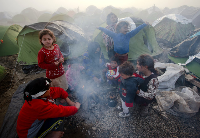 A child stretches on a foggy morning at the northern Greek border station of Idomeni, Friday, March 11, 2016. After nearly three days of rain, conditions in the refugee camp on the Greek-Macedonian where about 14,000 people are stranded have deteriorated significantly, with many of its residents struggling to re-pitch their small camping tents in slightly drier patches. (Photo by Vadim Ghirda/AP Photo)