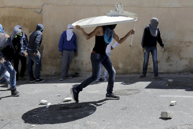 A Palestinian youth uses a satellite dish as a shield during clashes in the East Jerusalem neighbourhood of A-tur after a Palestinian youth was killed by Israeli security forces April 25, 2015. Israeli security forces killed the youth on Saturday as he tried to attack them with a knife at a checkpoint in the Jerusalem area, police said. (Photo by Ammar Awad/Reuters)