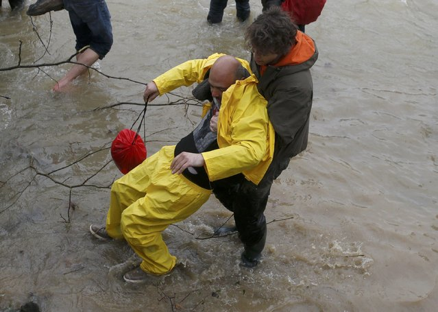 A migrant is helped as he wades across a river near the Greek-Macedonian border, west of the the village of Idomeni, Greece, March 14, 2016. (Photo by Stoyan Nenov/Reuters)