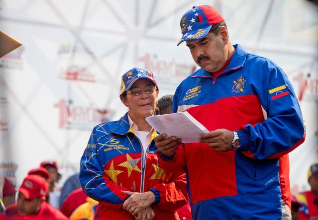 Venezuela's President Nicolas Maduro, right, reads a document as first lady Cilia Flores looks after they arrived for a May Day rally in Caracas, Venezuela, Friday, May 1, 2015. Maduro said at the rally he would raise the minimum wage and pensions for retirees by 30 percent, bringing the minimum wage to around 6,700 bolivars per month. (Photo by Fernando Llano/AP Photo)