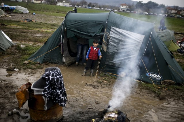 A refugee boy stands outside a tent at a makeshift camp for refugees and migrants at the Greek-Macedonian border, near the village of Idomeni, Greece March 16, 2016. (Photo by Alkis Konstantinidis/Reuters)