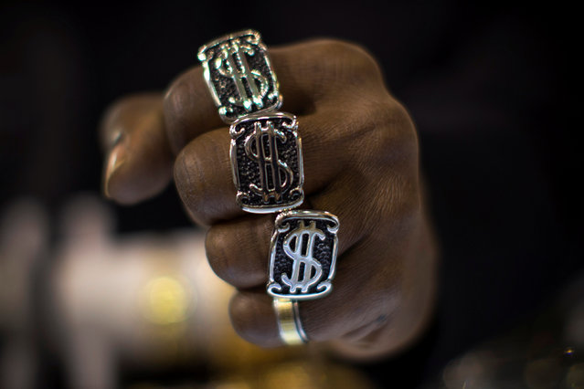 A man wears U.S. dollar sign rings in a jewellery shop in Manhattan in New York City November 6, 2014. (Photo by Mike Segar/Reuters)