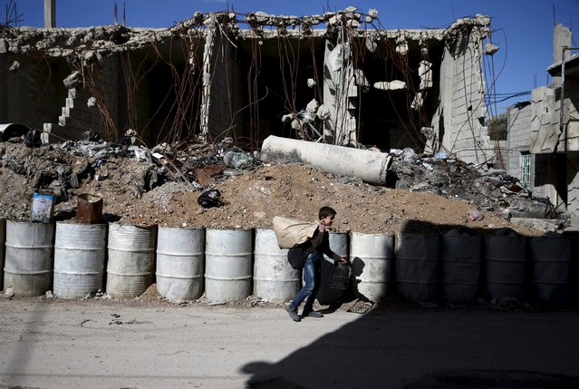 A boy walks past a damaged building in the rebel-held Tishreen neighborhood of Damascus, Syria March 14, 2016. (Photo by Bassam Khabieh/Reuters)