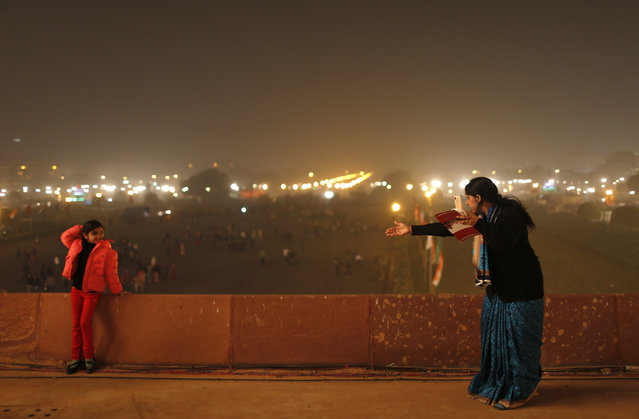 "A mother directs her daughter to pose for a photo at the venue for the ""Beating the Retreat"" ceremony in New Delhi January 29, 2014. The ceremony symbolises retreat after a day on the battlefield, and marks the official end of the Indian Republic Day celebrations. (Photo by Ahmad Masood/Reuters)"