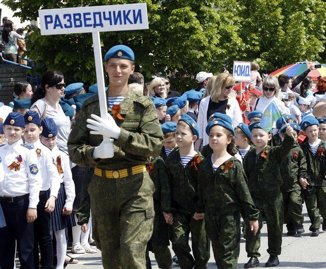 A man in a military uniform with a sign reading Scouts marches with children wearing specially made uniforms during the so-called Kid Parade in Rostov-on-Don, Russia, Thursday, May 14, 2015. (Photo by AP Photo/Stringer)