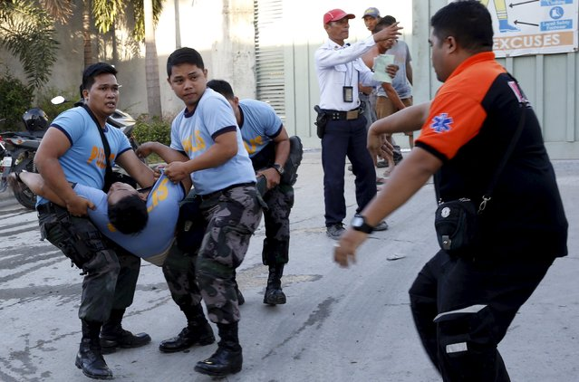 Police carry a colleague who collapsed while retrieving bodies of workers killed during a fire at a slipper factory in Valenzuela, Metro Manila in the Philippines May 14, 2015. A fire at a factory making rubber slippers killed 31 workers in the Philippine capital on Wednesday, and dozens were missing and feared dead, officials said. (Photo by Erik De Castro/Reuters)