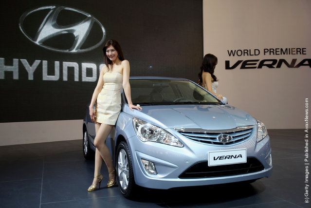 Two models stand beside the world premiere display of Hyundai VERNA car