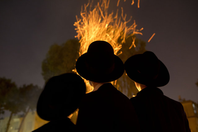 Ultra-Orthodox Jews gather next to bonfires during the Jewish holiday of Lag Ba'Omer celebration in Bnei Brak, Israel, Wednesday, May 22, 2019. The holiday marking the end of a plague said to have decimated Jews during the Roman times. (Photo by Oded Balilty/AP Photo)