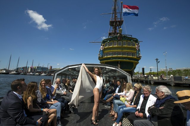 Dutch model Lisa van Heijningen, 23, presents a creation of Israeli brand Gottex, as a 17th century Dutch East India Company (VOC) ship is seen in the background, during the Canal Catwalk at the Floating Fashion Week in Amsterdam, Netherlands May 21, 2015. (Photo by Cris Toala Olivares/Reuters)