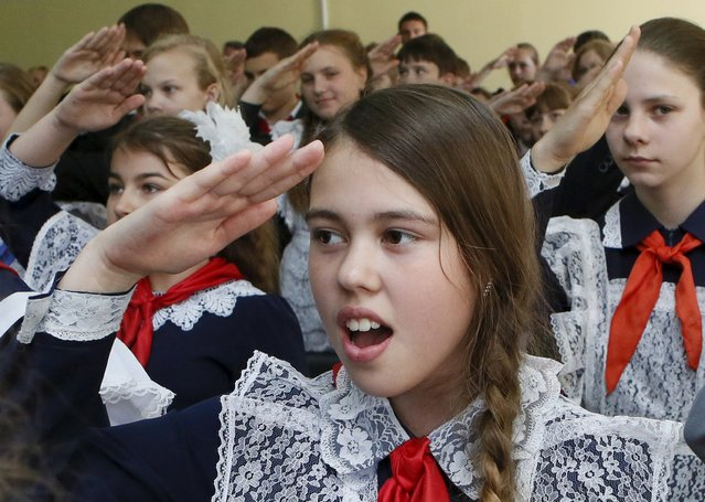 Children, wearing red neckerchiefs, a symbol of the Young Pioneer Organisation, salute during a ceremony for the inauguration of 45 newly adopted members on the day of its anniversary at school-lyceum number 12 in the Siberian city of Krasnoyarsk, Russia, May 19, 2015. (Photo by Ilya Naymushin/Reuters)