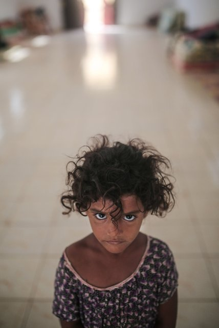 In this Wednesday, May 20, 2015 photo, Aseya, 3, poses for a photo in her family's room in at an orphanage that has been turned into a center for Yemeni refugees, in Obock, northern Djibouti. Fleeing the war at home, thousands of Yemenis have made it across the Gulf of Aden to find refuge in Djibouti, a sleepy Horn of Africa nation where the United Nations has set up a staging hub for aid for the conflict-torn Arab country. (Photo by Mosa'ab Elshamy/AP Photo)
