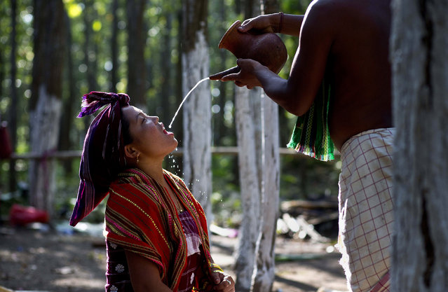 In this Monday, June 10, 2019 photo, an Indian Rabha tribal Hindu priest pours traditional rice beer to a Rabha girl to perform rituals during Baikho festival at Pantan village, west of Gauhati, India. Every year, the community in India's northeastern state of Assam celebrates the festival, to please a deity of wealth and ask for good rains and a good harvest. (Photo by Anupam Nath/AP Photo)