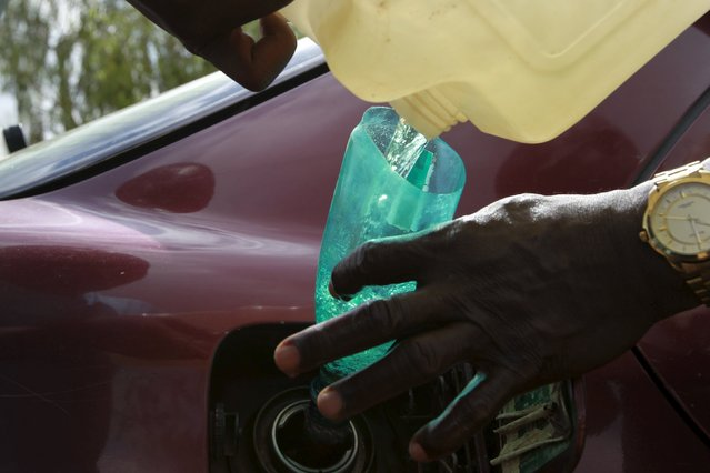 A man pours petrol into a car tank outside the NNPC mega petrol station in Abuja, Nigeria May 25, 2015. (Photo by Afolabi Sotunde/Reuters)