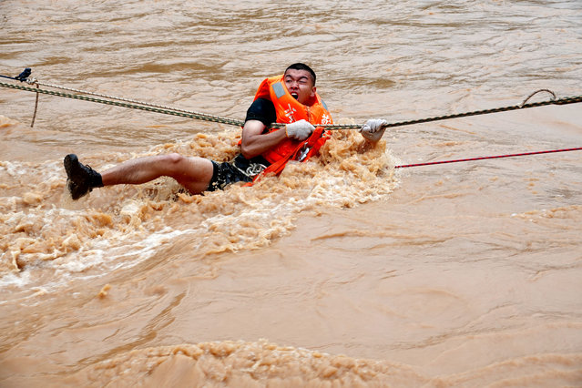 Chinese rescuers evacuate a local resident in floodwater caused by a heavy rainstorm in Heyuan city, south China's Guangdong province, 13 June 2019. At least 24 people are dead with others missing after yet another round of heavy rain struck southern China. More downpours threaten to exacerbate the flooding situation across the region through the remainder of the month. An estimated 2.2 million people have been affected by the onslaught of heavy rain and flooding that commenced last Thursday, according to UPI. (Photo by Feature China/Barcroft Media/Imaginechina via AP Images)