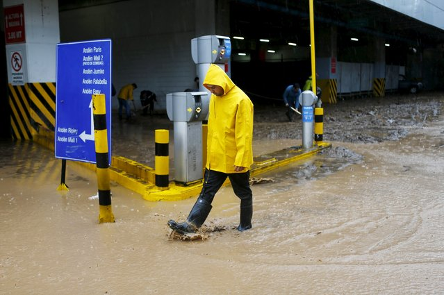 A man walks out from a flooded commercial center access in Santiago, April 17, 2016. (Photo by Ivan Alvarado/Reuters)