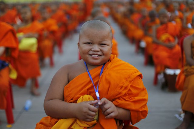 Buddhist novice poses for a picture while monks gather to receive alms at Wat Phra Dhammakaya temple, in what organizers said was a meeting of over 100,000 monks, in Pathum Thani, outside Bangkok April 22, 2016. (Photo by Jorge Silva/Reuters)