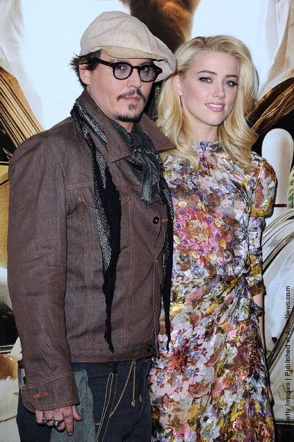 Johnny Depp and Amber Heard pose as they attend the 'Rhum Express' Photocall at Hotel Paris Plaza Athenee