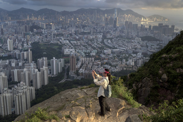 In this photograph taken on June 28, 2015, a hiker in Hong Kong takes a picture of the city from a walking trail. The southern Chinese territory is crisscrossed by more than 180 miles of designated hiking trails. (Photo by Alex Ogle/AFP Photo)