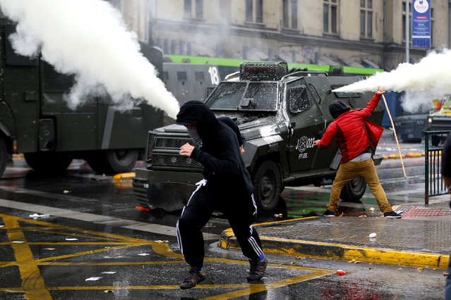 Demonstrators clash with riot police vehicles during a rally commemorating May Day in Santiago, Chile May 1, 2016. (Photo by Ivan Alvarado/Reuters)
