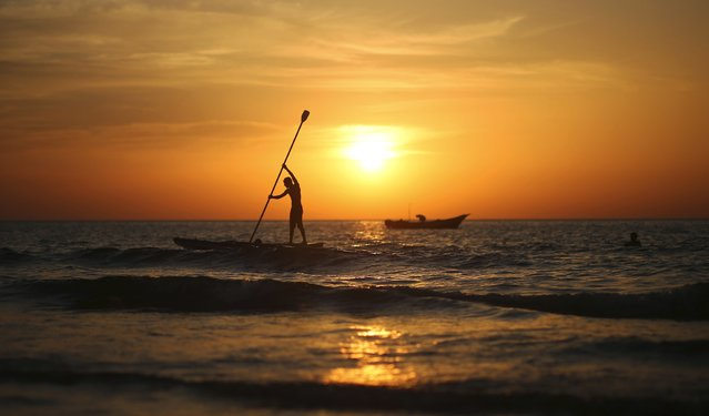 A Palestinian man paddles a traditional boat in the Mediterranean Sea off the coast of Gaza City April 18, 2014. (Photo by Mohammed Salem/Reuters)