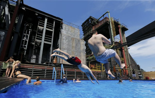 Boys jump into the Works Swimming Pool in the yard of the former coking plant of the Zeche Zollverein UNESCO world heritage site in Essen, Germany, July 1, 2015. The Works swimming pool created by the two Frankfurt artists Daniel Milhonic and Dirk Paschke is made of two regular ship containers. The 13 by 5 m long, 2.4 m deep pool is open during the summer and admittance is free of charge. (Photo by Wolfgang Rattay/Reuters)