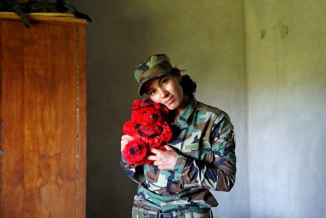 Yazidi female fighter Asema Dahir, 21, poses with a teddy bear in a bedroom at a site near the frontline of the fight against Islamic State militants in Nawaran near Mosul, Iraq, April 20, 2016. (Photo by Ahmed Jadallah/Reuters)