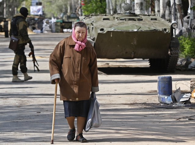 "An elderly woman walks in the center of Slovyansk, eastern Ukraine, Wednesday, April 23, 2014. Pro-Russian gunmen in eastern Ukraine admitted on Wednesday that they are holding American journalist Simon Ostrovsky, saying he was suspected of unspecified ""bad activities"". (Photo by Sergei Grits/AP Photo)"