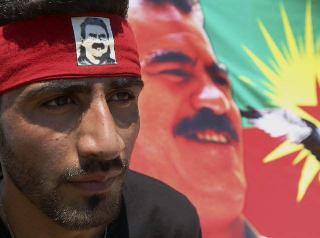 A Kurdish man who lives in Lebanon wears a headband with a photo of the jailed Turkish Kurdish guerrilla leader Abdullah Ocalan, standing by a poster of him, during a demonstration in solidarity with their Kurdish brethren in northern Syria who are fighting against Islamic State group militants, in front of the United Nations headquarters in Beirut, Lebanon, Sunday, July 5, 2015. (Photo by Bilal Hussein/AP Photo)