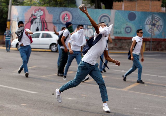 A student throws a rock during a protest to demand the government to repeal a law that requires high school seniors to teach at least two people to read and write, as part of a graduation programme in Tegucigalpa, Honduras, May 4, 2016. (Photo by Jorge Cabrera/Reuters)