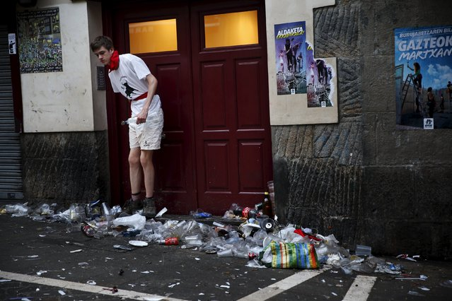 A reveller leaves a building surrounded by garbage before the first running of the bulls of the San Fermin festival in Pamplona, northern Spain, July 7, 2015. (Photo by Susana Vera/Reuters)