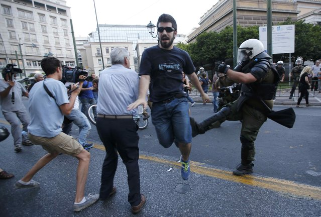 Anti-Euro protesters scuffle with riot police officers as they attend an anti-austerity rally in central Athens, Greece, July 10, 2015. Greek Prime Minister Alexis Tsipras appealed to his party's lawmakers on Friday to back a tough reforms package after abruptly offering last-minute concessions to try to save the country from financial meltdown. (Photo by Jean-Paul Pelissier/Reuters)