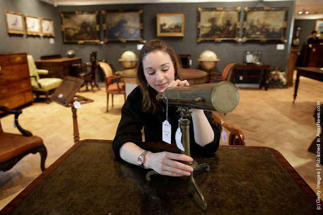 Bonhams employee Victoria Livesey looks at a Gregorian Reflecting Telescope from the early 19th century