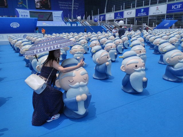 A citizen poses with artoon Confucius figures displayed during the 12th China (Shenzhen) International Cultural Industry Fair (ICIF) at Shenzhen Convention & Exhibition Center on May 12, 2016 in Shenzhen, Guangdong Province of China. (Photo by VCG/VCG via Getty Images)
