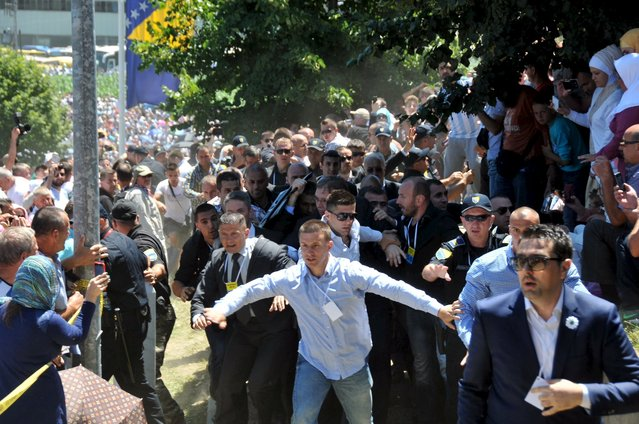 Bodyguards protect Serbia's Prime Minister Aleksandar Vucic during unrest at a ceremony marking the 20th anniversary of the Srebrenica massacre, in Potocari, near Srebrenica, Bosnia and Herzegovina July 11, 2015. Vucic was forced to flee the ceremony on Saturday, when mourners hurled stones and bottles at him in what his government later described as an attempted assassination. (Photo by Ivan Sebalj/Reuters/Avaz)