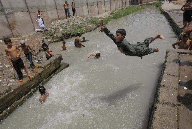 Pakistani children cool themselves off in a stream in Peshawar, Pakistan, Monday, June 29, 2015, during Muslim's fasting month of Ramadan. (Photo by Mohammad Sajjad/AP Photo)